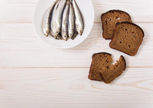 Солим кильку на белой тарелке с черным хлебом. минималистичный стиль. белый деревянный фон. скопировать пространство