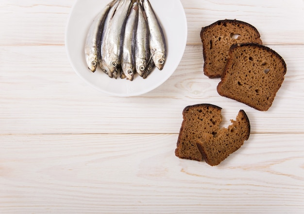 Salt sprat on the white plate with black bread. minimalist style. white wooden background.copy space