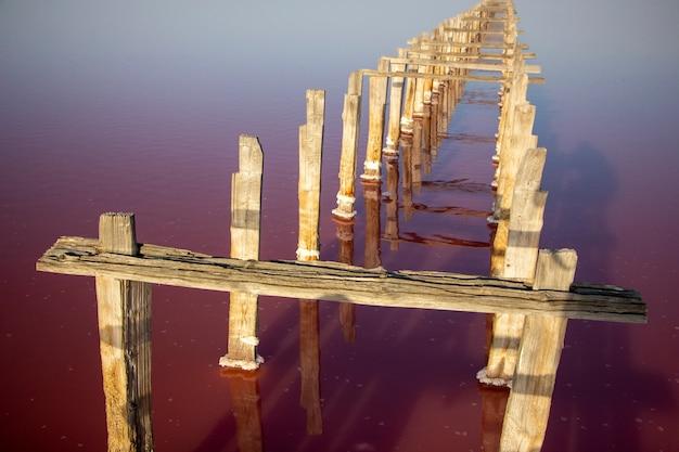핑크 소금으로 호수에 말린 나무 기둥으로 울타리를 친 소금 스트립
