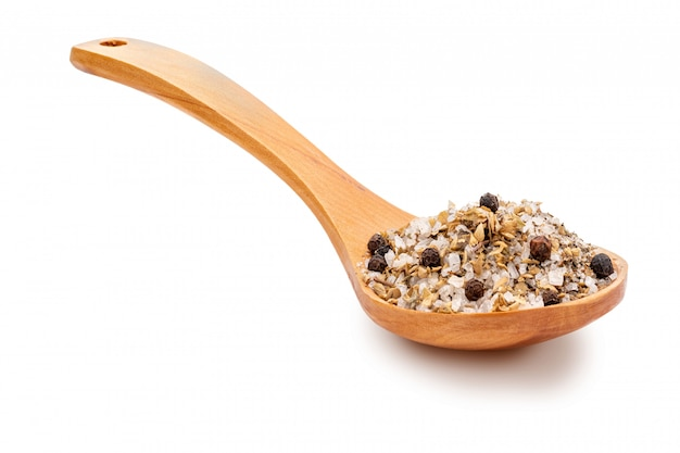 Salt with black pepper and dried basil in a wooden spoon.
