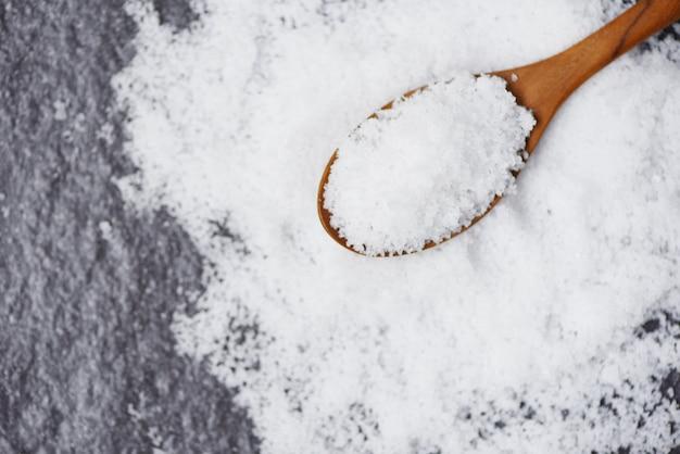 Salt in wooden spoon and heap of white salt on dark