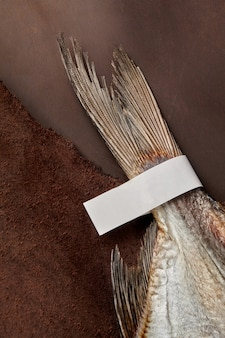 Salted airdried roach tail with paper label on brown leather background