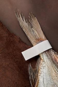 茶色の革の背景に紙ラベルと塩漬けの風乾ゴキブリの尾