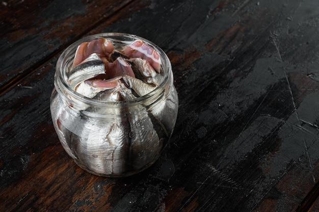 古い暗い木製のテーブルの上に、ガラスの瓶に塩漬けのアンチョビの切り身