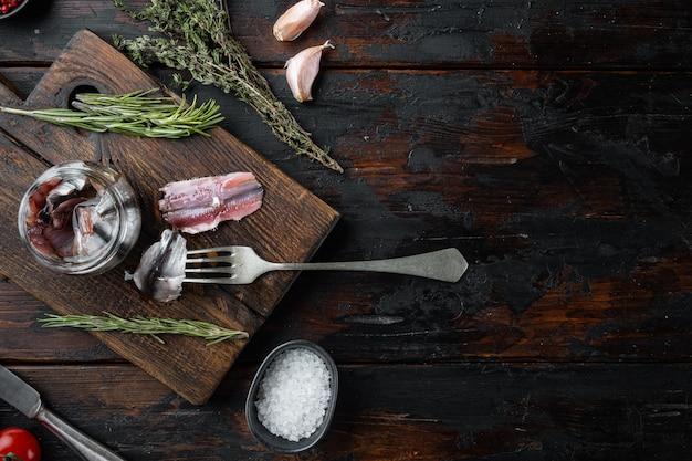 塩漬けのアンチョビの切り身、木製のまな板、古い暗い木製のテーブル