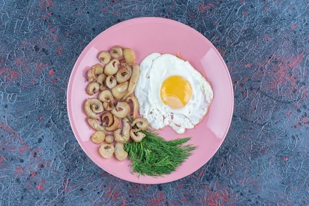 Жареное яйцо с солью и специями с петрушкой на розовой тарелке.