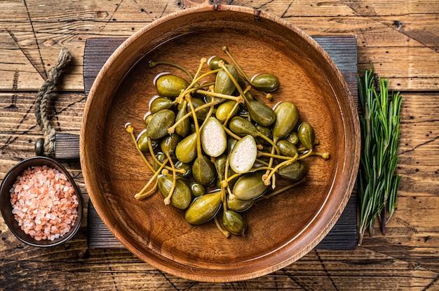 나무 접시에 식초에 소금에 절인 케이 퍼. 나무 배경입니다. 평면도.