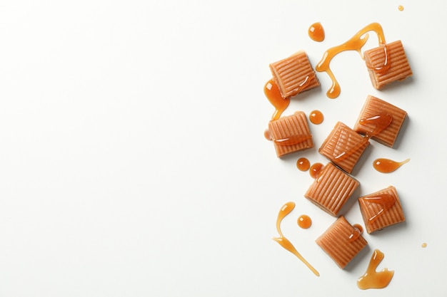 Salted caramel candies and sauce on white space, space for text