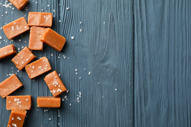 Salted caramel candies on wooden space, space for text