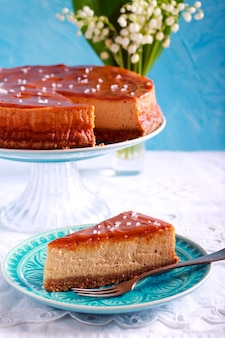 Salted caramel cheesecake, sliced on blue plate
