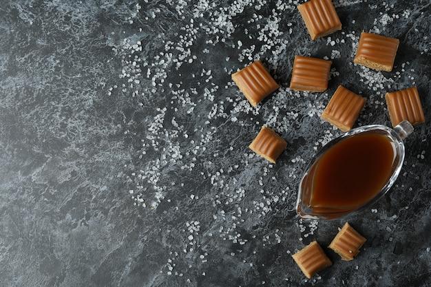 Кусочки соленой карамели и соус на черном дымном фоне