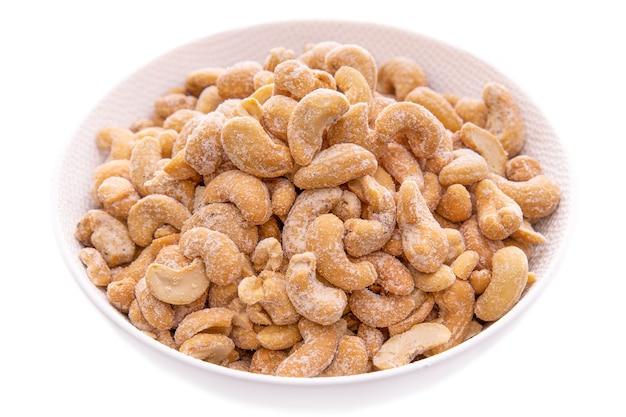 Соленые орехи кешью в белой миске крупным планом