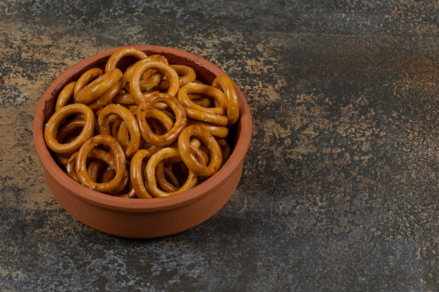 Salted circle pretzels in ceramic bowl.