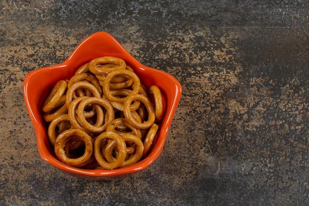 Salted circle pretzels in orange bowl.