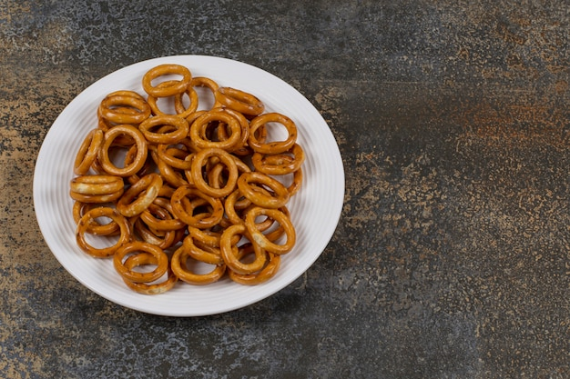 Salted circle pretzels on white plate.
