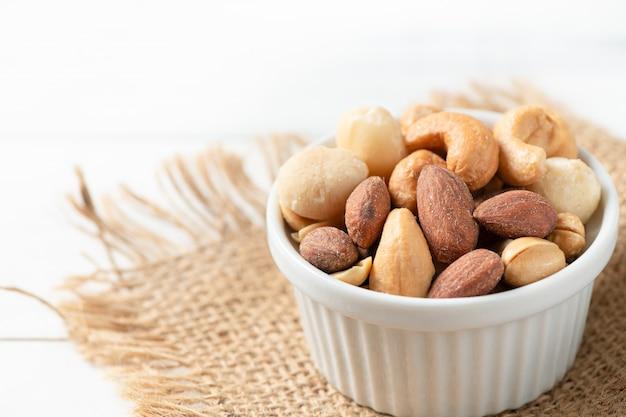 Соленые орехи коктейль на белом фоне древесины.