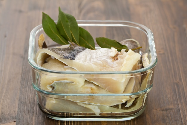 Salted cod fish in water in glass dish on brown