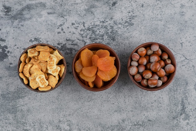 Salted crackers, dried apricots and hazelnuts in wooden bowls.