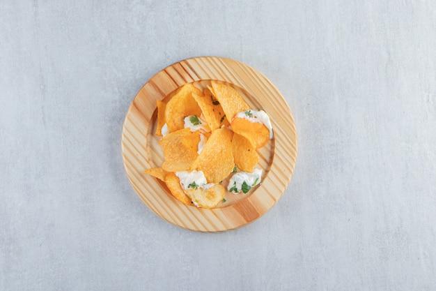 木の板に塩漬けのクリスピーチップスと新鮮なヨーグルト。
