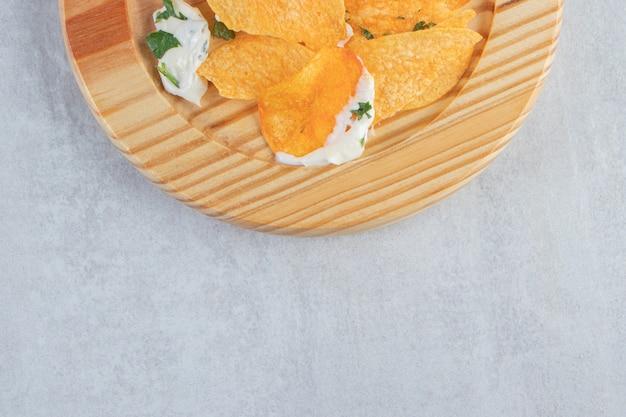 Patatine fritte croccanti salate e yogurt fresco sul piatto di legno.