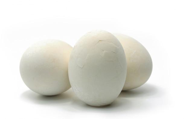 ゆでた塩漬け卵は、白い背景の上に置かれたシェルを割れています。