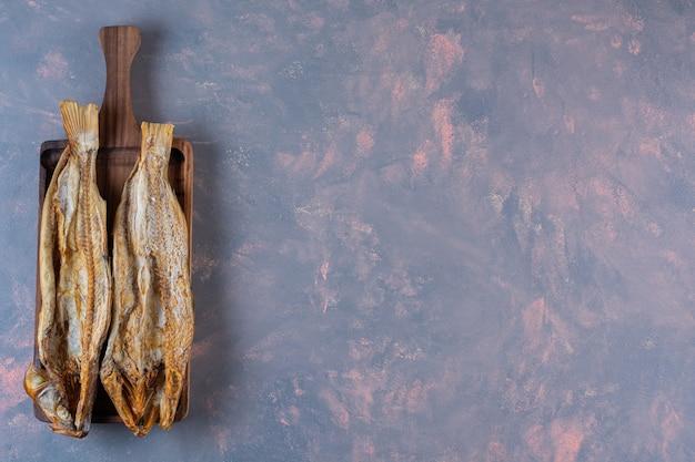 대리석 배경에 보드에 소금에 절인 생선.