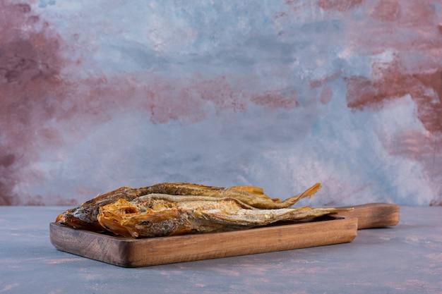 Соленая рыба на доске, на мраморной поверхности