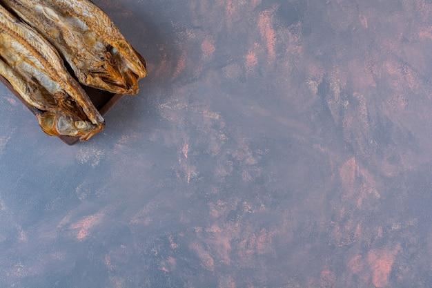 大理石の表面のボード上の塩漬けの魚