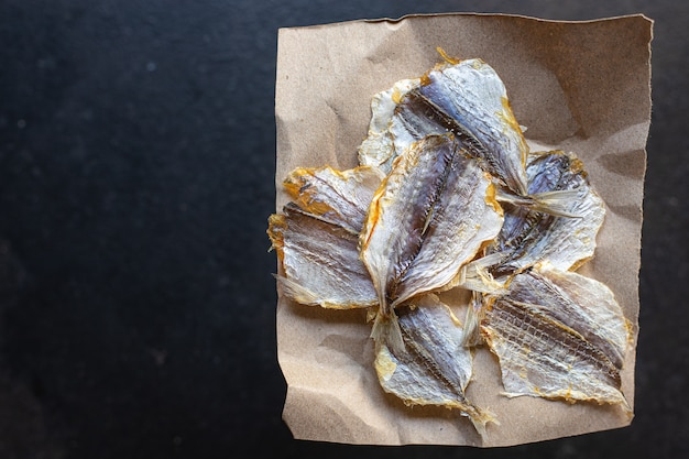 テーブルの上の塩漬けの魚の小さな乾燥日干しまたは燻製スナックミールコピースペース食品の背景