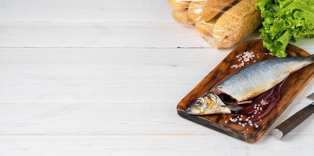Salted herring on a cutting board with bread and lettuce