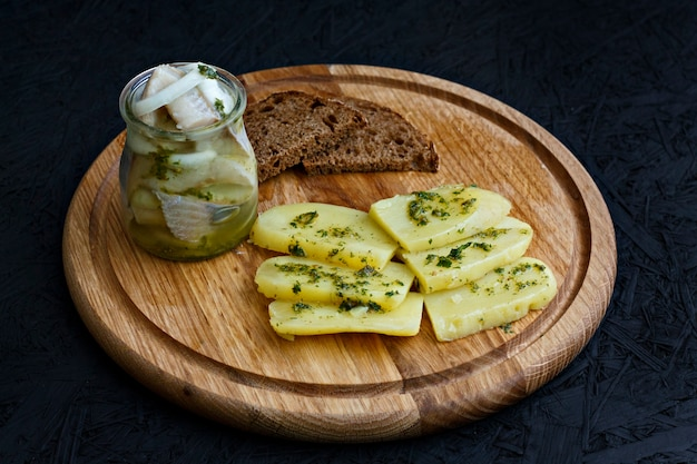 Salted herring in a jar with boiled potatoes and green sauce.