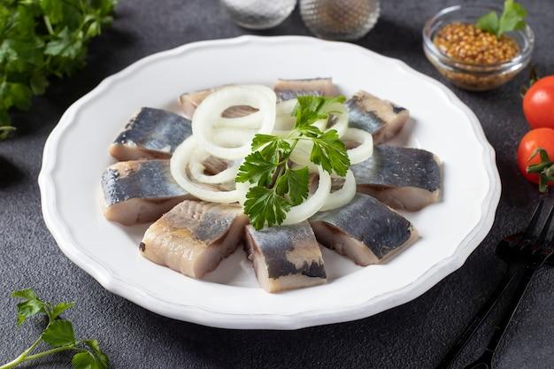 Кусочки соленой сельди с луковыми кольцами и петрушкой на белой тарелке на темно-сером фоне.