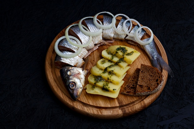Salted herring with boiled potatoes and green sauce.