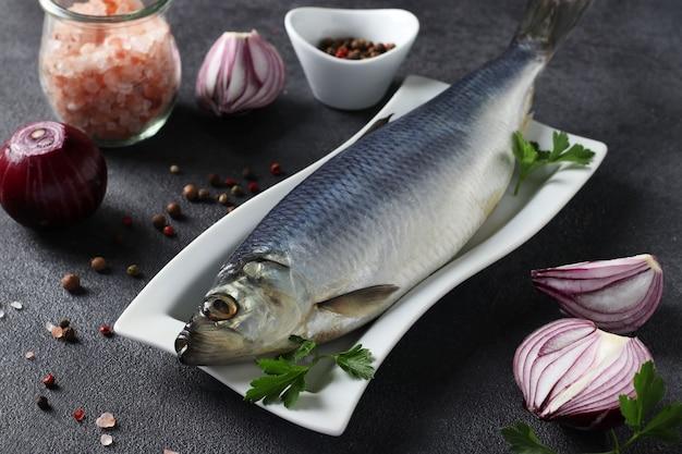 회색 배경에 붉은 양파, 후추, 바다 소금, 파슬리를 곁들인 소금에 절인 청어. 가로 형식