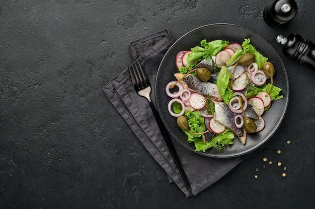 Соленая сельдь со специями, каперсами, зеленью и луковым салатом на черной тарелке на темном фоне