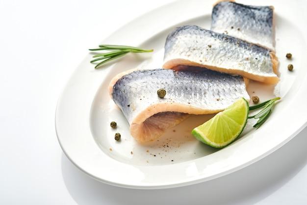 Соленая сельдь со специями, зеленью и луком на белой тарелке, изолированные на белом фоне