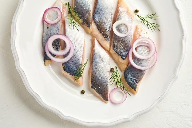 Соленая сельдь со специями, зеленью и луком на белой тарелке на светлом каменном фоне с копией пространства. маринованная нарезанная рыба. еда со здоровыми ненасыщенными жирами, плоская форма