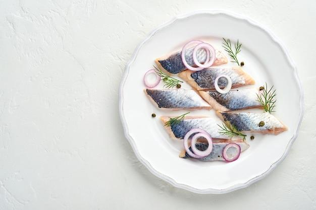 Соленая сельдь со специями, зеленью и луком на белой тарелке на светлом каменном фоне