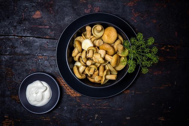 Соленые молочные грибы с зелеными веточками укропа в черной миске и сметаной в блюдце на черном деревянном столе