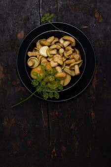 Соленые молочные грибы с зелеными веточками укропа в черной миске на черном деревянном столе
