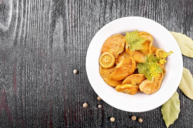 Соленые грибы шафран со сметаной, листом смородины и веточкой укропа в тарелке, лавровым листом и перцем на фоне деревянной доски сверху