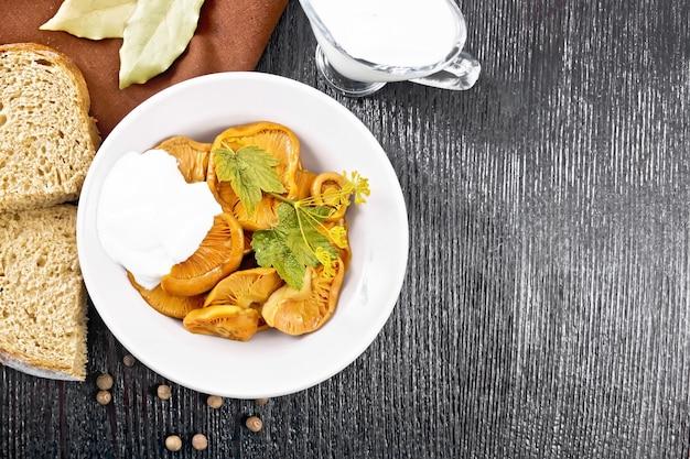 Шафран соленые грибы со сметаной, листом смородины и веточкой укропа в тарелке, вилке, полотенце и хлебе