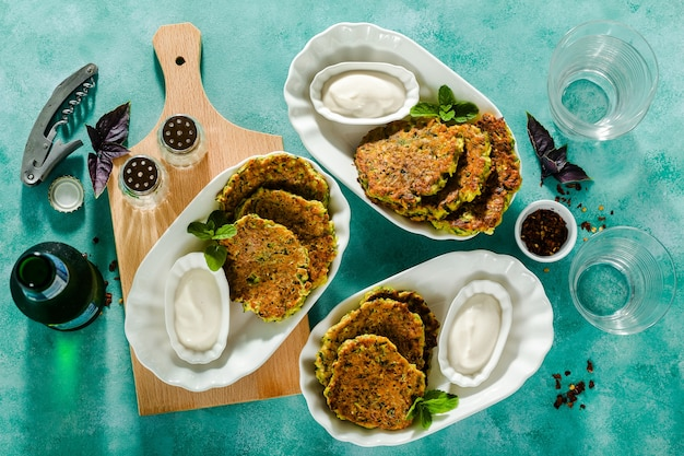 Salted pancakes with zucchini and chickpea flour and spicy yogurt sauce with beer