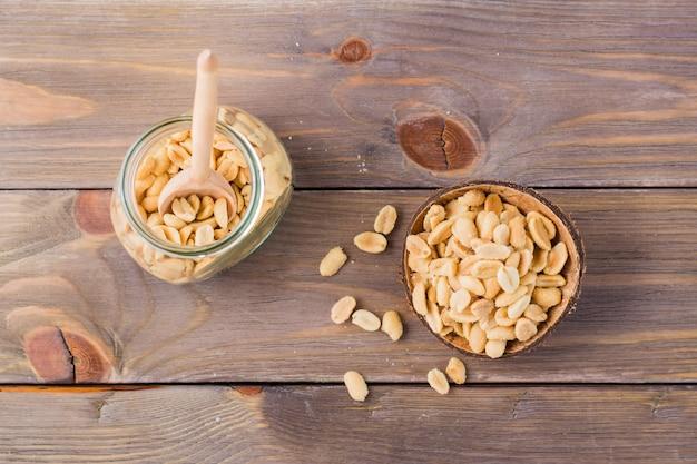 ボウルと木製のテーブルの上の瓶に塩漬けのピーナッツ。健康的なベジタリアン料理。素朴なスタイル。上面図