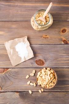 木製のテーブルの上の紙の上にスプーンと塩を入れたボウルと瓶の中の塩漬けピーナッツ。健康的なベジタリアン料理。素朴なスタイル。垂直および上面図