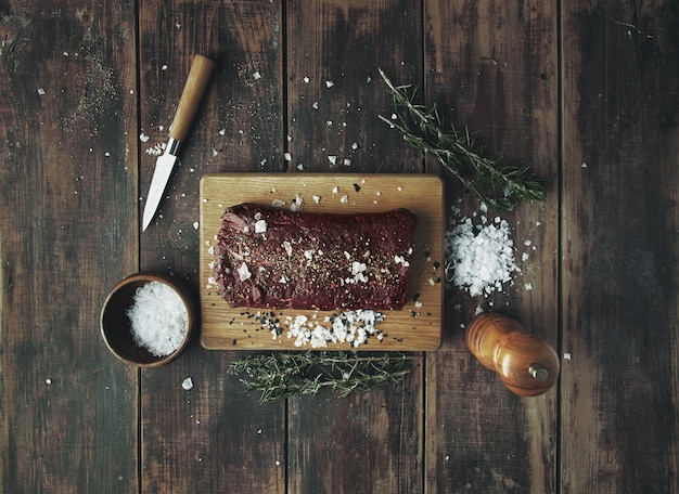 Salted peppered piece of meat ready to grill on wooden table between herbs and spices on wooden