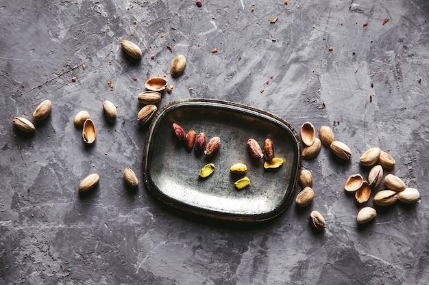 Salted pistachiosin an iron plat. selective focus.