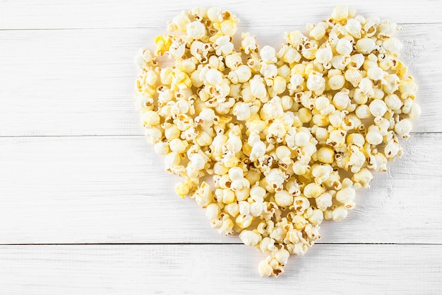 Salted popcorn in the shape of heart on a white table. top view.