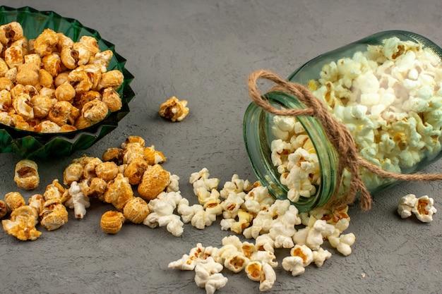 Popcorn salato con popcorn dolce squisito all'interno della latta di vetro e piatto verde su un grigio
