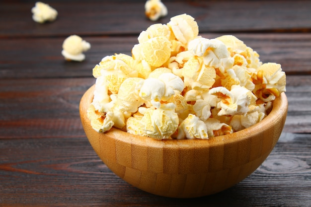 Salted popcorn in a wooden bowl on a wooden table.